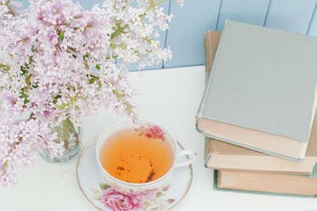 Libros antiguos, montón suave de color lila y taza de té de porcelana en la mesa en el fondo de madera azul Foto de archivo - 45360596
