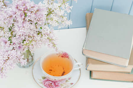 vintage books, gentle bunch of lilac and china teacup on the table on blue wooden background