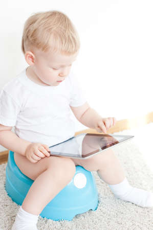 depend: little boy on potty with tablet pc on the  white carpet Stock Photo