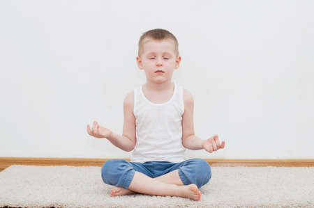 Kid doing yoga relaxing exercise in his room