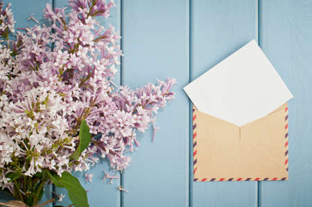 purple: vintage postage envelope with card and beautiful summer blooming bouquet of lilac