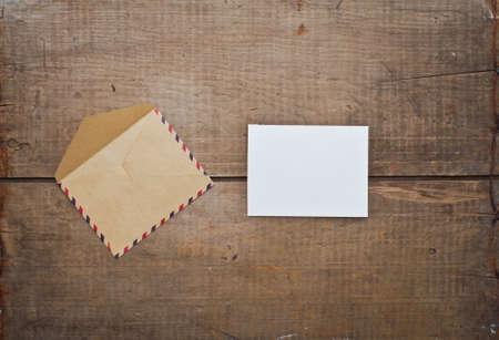 Sobre de la vendimia y de la tarjeta en el fondo de madera Foto de archivo - 45360463