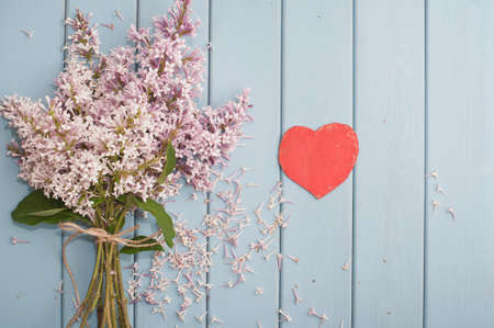 love pic: Red wooden heart and summer blooming bouquet of lilac on blue wooden background
