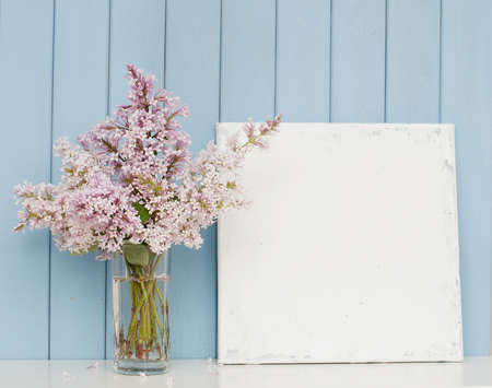 vases: Gentle bunch of lilac in glass and blank canvas on the table on blue wooden background