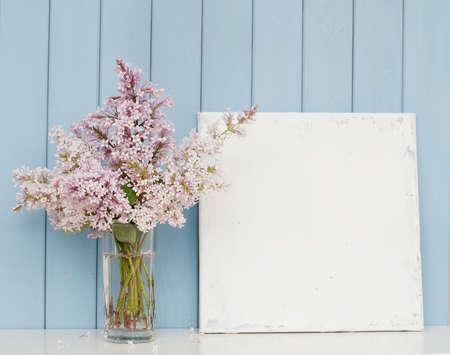 Mucchio delicato di lillà in vetro e tela bianca sul tavolo di legno su sfondo blu Archivio Fotografico - 45360469