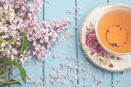 Summer blooming bouquet of lilac and china cup with black tea
