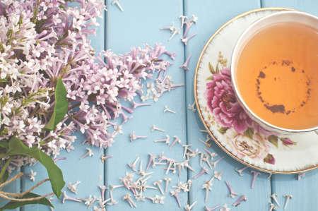 rosas negras: Verano en flor ramo de lilas y taza de porcelana con té negro Foto de archivo