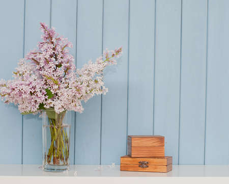 Two vintage wooden boxes and bunch of lilac on the table