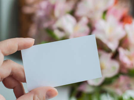 Hand holding blank greeting card and flowers in the background Stock Photo
