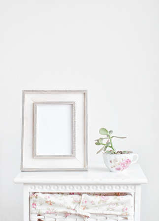 Home decoration, picture frame and plant on the bedside table