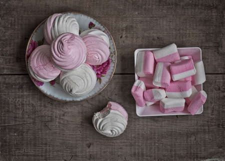kiss biscuits: Delicate meringues and pink marshmallows on old vintage wooden table