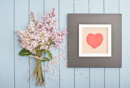 love pic: Black wooden vintage picture frame with red heart and  summer blooming bouquet of lilac Stock Photo