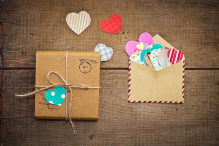 missive: vintage envelope with colorful hearts and parcel on wooden background