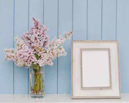 Marco de la vendimia y el manojo de lila en la mesa en el fondo de madera azul Foto de archivo - 45359887