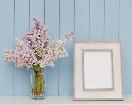 Vintage picture frame and bunch of lilac on the table on blue wooden background