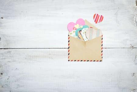 old envelope: old vintage envelope with colorful hearts on wooden background