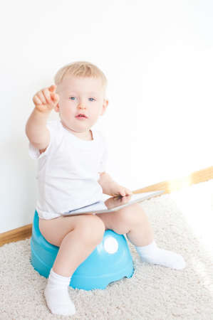 wee: little boy on potty with tablet pc on the  white carpet Stock Photo