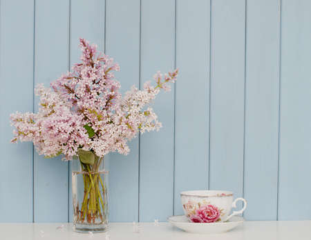Gentle bunch of lilac and china teacup on the table on blue wooden background Stock Photo