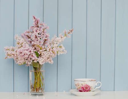 Montón suave de color lila y taza de té de porcelana en la mesa en el fondo de madera azul Foto de archivo - 45357890