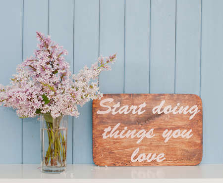 Vintage poster with inspiring words and romantic gentle bunch of lilac on the table Stock Photo