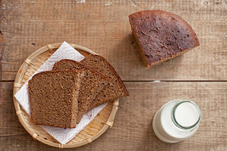 brown bread: Bottle of milk and slices of rye brown bread on rustic wooden table
