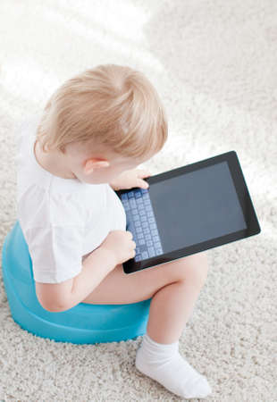 depending: little boy on the chamder with tablet pc on the  white carpet Stock Photo