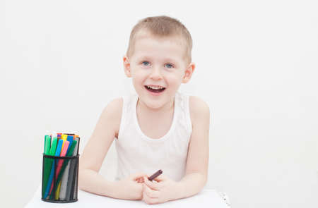 4 years old: Laughing 4 years old kid is drawing Stock Photo