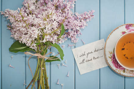 come in: Motivational card quote i wish your dreams will come true in summer bouquet of gentle blooming lilac  and tea in china teacup with saucer
