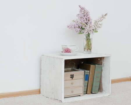 curio: gentle bunch of lilac and china teacup on vintage shabby nightstand with wooden box and ancient books inside