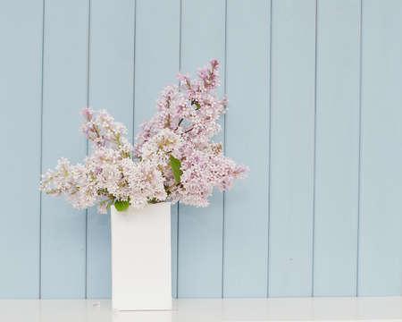 푸른 나무 배경에 테이블에 흰색 꽃병에 라일락의 부드러운 무리 스톡 콘텐츠