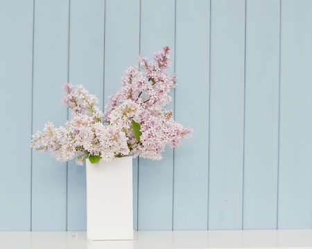 Gentle bunch of lilac in white vase on the table on blue wooden background