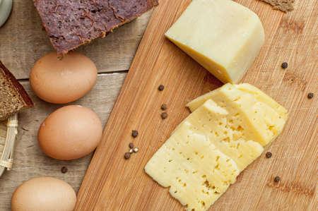 gallina con huevos: R�bano rojo, botella de leche, pan de centeno, queso, huevos de gallina en mesa de madera