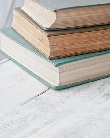 spines: old vintage antique books pile on white wooden tabe Stock Photo