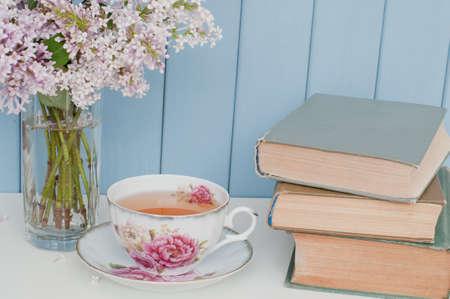 Montón suave de color lila, libros antiguos y taza de té de porcelana en la mesa en el fondo de madera azul