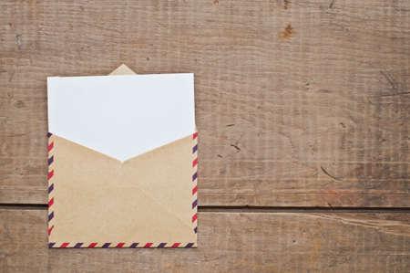 Sobre de la vendimia y de la tarjeta en el fondo de madera Foto de archivo - 45357568