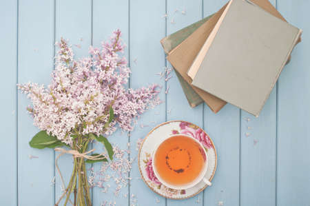 ancient books: ancient books, black tea in china teacup and summer blooming bouquet of lilac