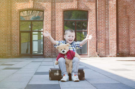 4 years old: Happy little 4 years old boy sitting on suitcase with teddy bear  on street stone pavement Stock Photo