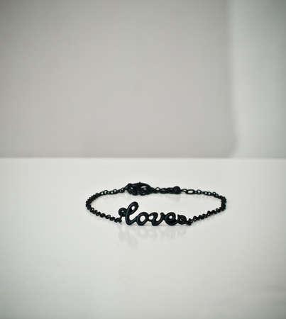 wrist strap: Black bracelet with word love on white  background