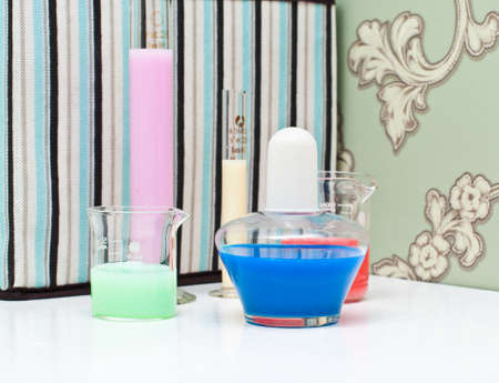 liquids: Tubes, bulb and measuring glass with colorful  liquids on the many-colored background Stock Photo