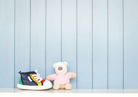 babys: Tiny Babyschuhe und Teddybär auf dem Tisch im Kinderzimmer