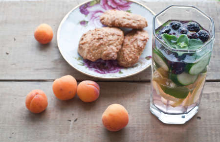 sassy: oat biscuits, apricots and fresh cold lemonade, fruit sassy water with lemon, cucumber, peppermint and blackberries on wooden background