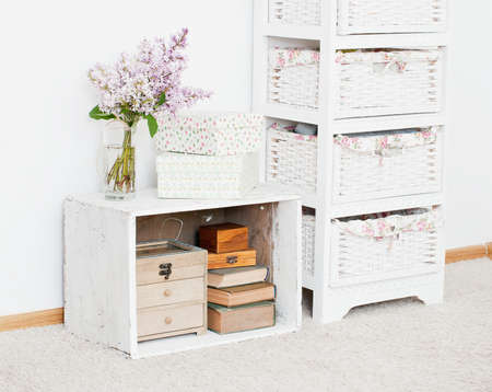 curio: Vintage nightstand with flowers, storage boxes and ancient books Stock Photo