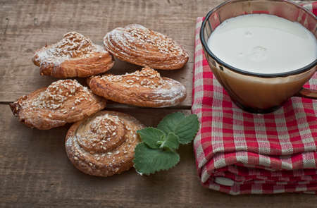 gingham: Festive sweets, puff cookies with sesame seeds and milk on gingham table cloth Stock Photo