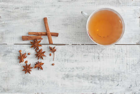 christmas perfume: cinnamon stick, star anise and cup of tea on wooden table Stock Photo
