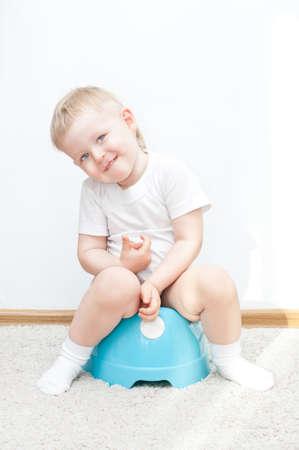 potty: little cute smiling boy on blue potty. have toilet