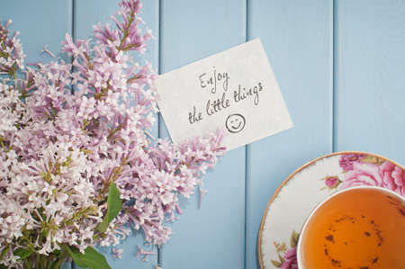 teacup: Motivational card quote enjoy the little things in summer bouquet of gentle blooming lilac  and tea in china teacup with saucer Stock Photo