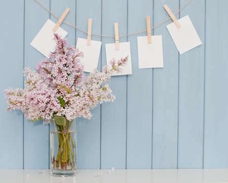 empty photographs on the clothespin and romantic bunch of lilac on the table