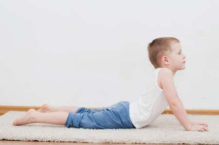 bhujangasana: Kid doing yoga relaxing exercise in his room