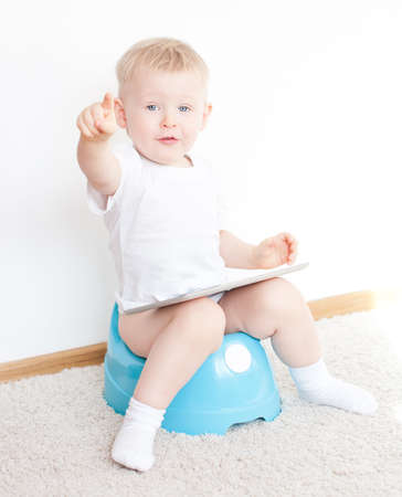 little boy on potty with tablet pc on the  white carpet Stock Photo