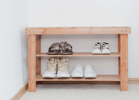 Old vintage wooden bench with shoes shelf, storage of shoes on the shelf Stock Photo